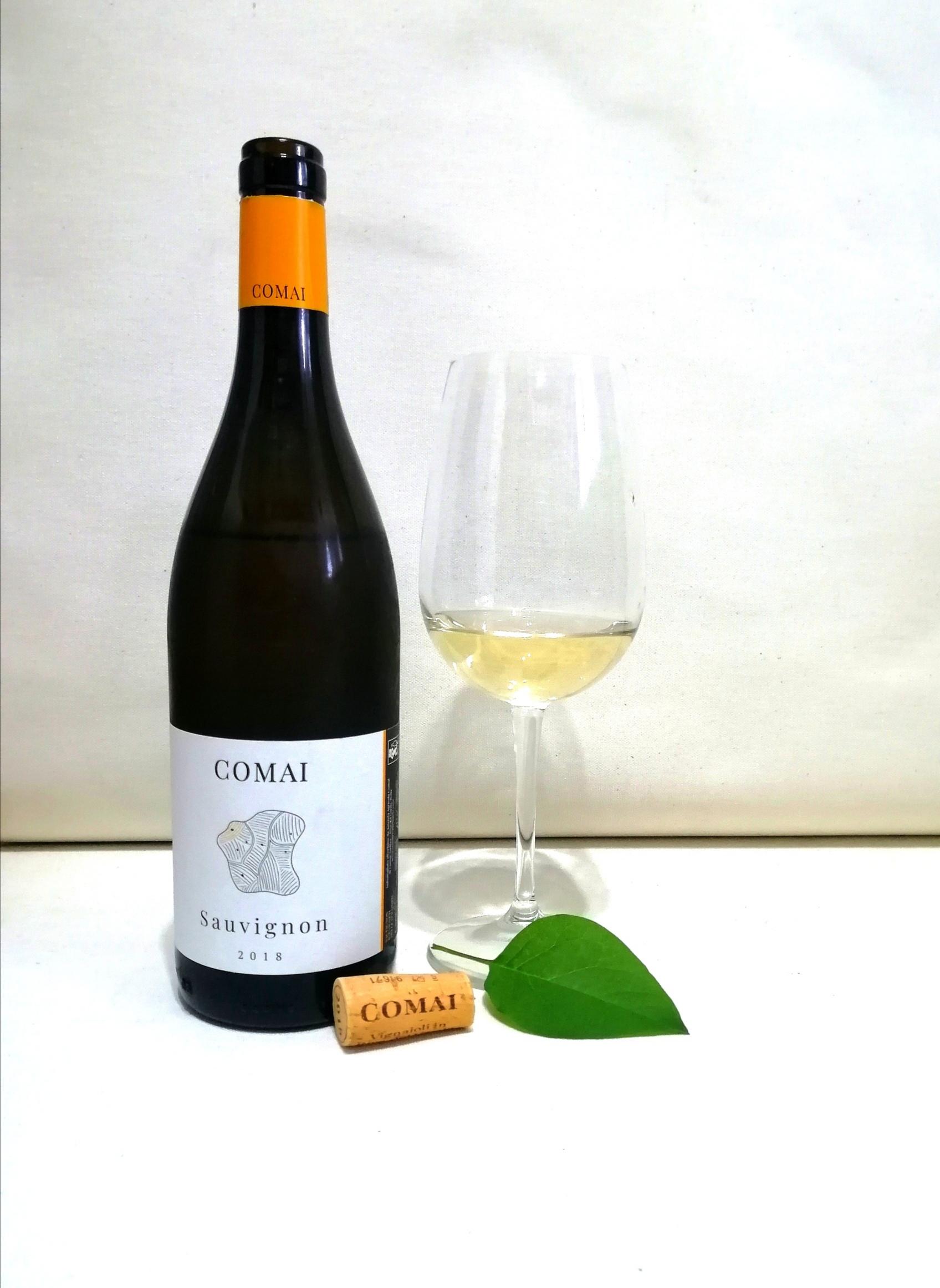 Bottiglia di sauvignon della cantina Comai e bicchiere di vino