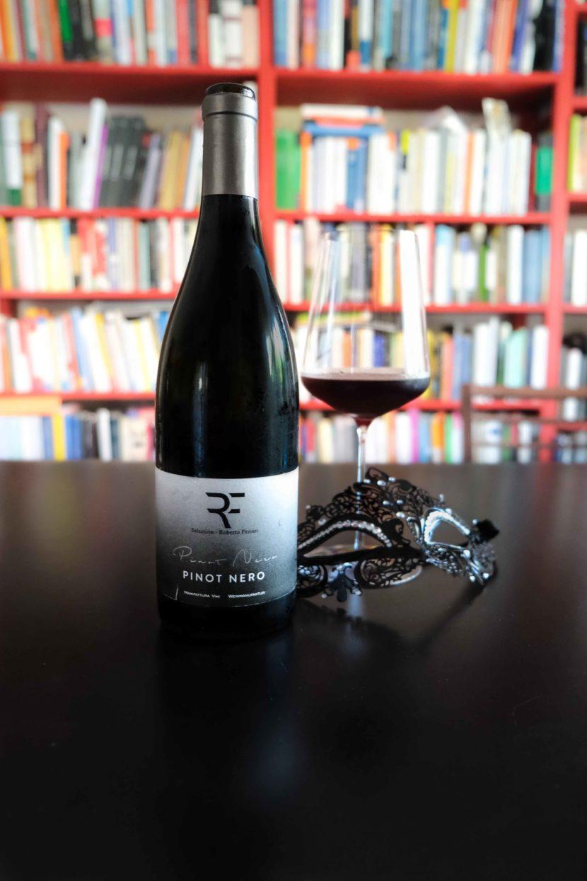 Una bottiglia di Pinot Nero di Roberto Ferrari con una maschera